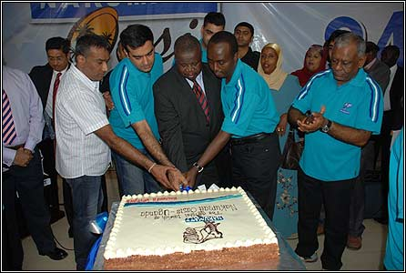 Minister of trade Kahinda Otafire cutting the cake with Nakumatt staff