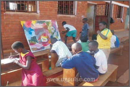 A child paints on a large canvas in the Kisa school yard, while others draw some of their ideas on paper