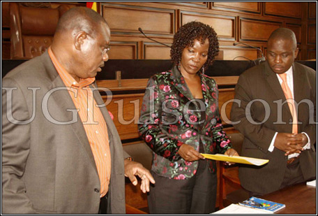 Lukwago(R) watches as Musisi(C) receives instruments of power from Sebaggala(L)